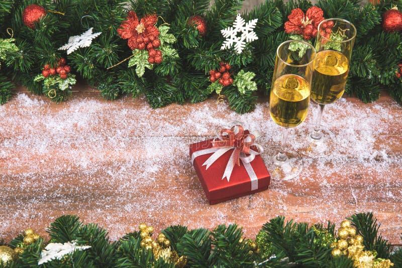 Champagne due vetri e un contenitore di regalo rosso nel mezzo di legno nevoso immagini stock