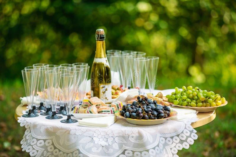 Champagne e uvas em uma tabela de bufete foto de stock