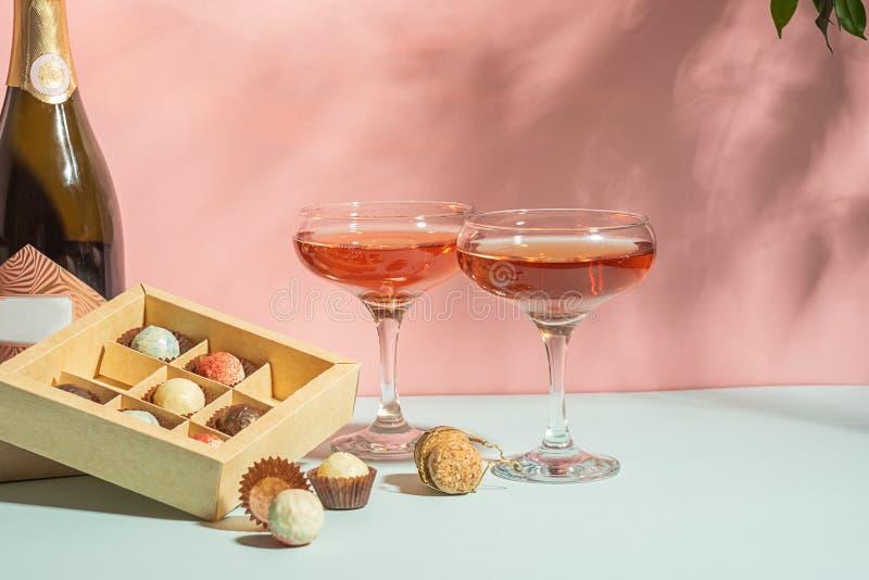 Champagne eller vin i eleganta exponeringsglas, en ask av rosa bakgrund f?r choklader av ljust ljus kopiera avst?nd Selektivt fok royaltyfri foto