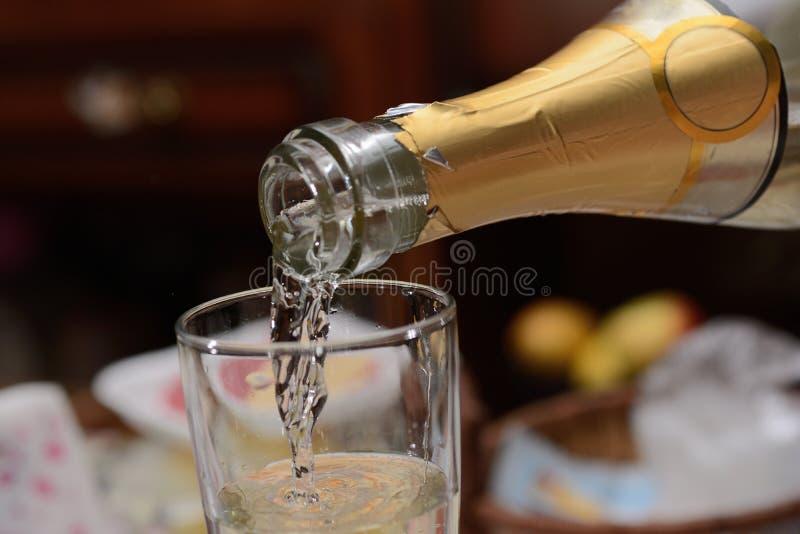 Champagne est versée dans un verre, fin  image libre de droits