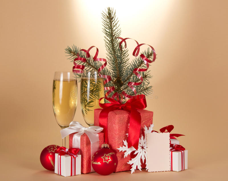 Champagne, fir-tree branch, gifts. Champagne, fir-tree branch with tinsel, gift boxes, toys and blank card on a beige background royalty free stock images