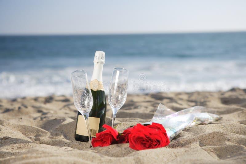 Champagne-Flasche, Gläser, Rosen am Strand lizenzfreie stockfotos