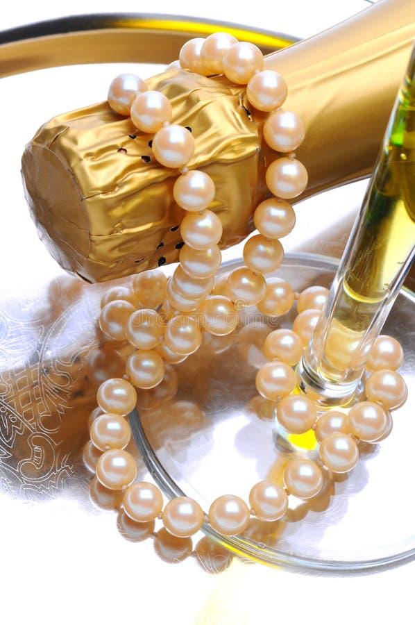 Champagne-Flaschenglas und Perlen lizenzfreie stockfotografie