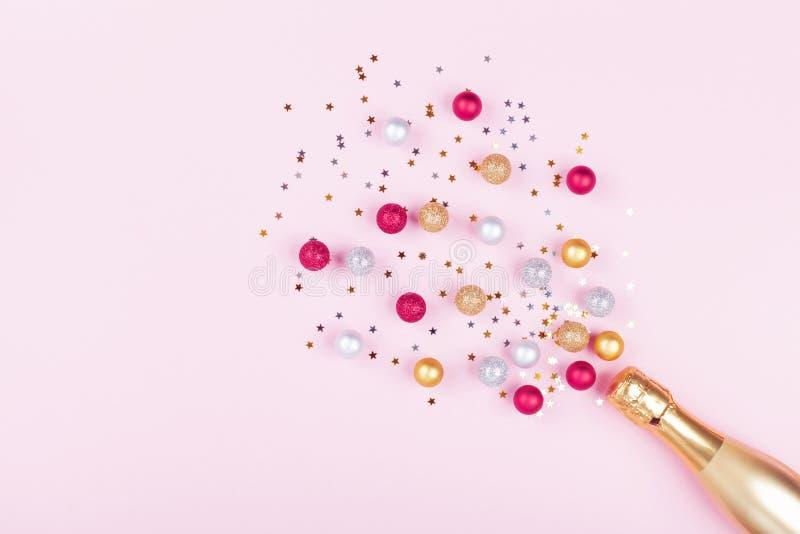 Champagne-fles met confettiensterren en vakantieballen op pastelkleur roze achtergrond Het patroon van Kerstmis vlak leg stijl stock foto's