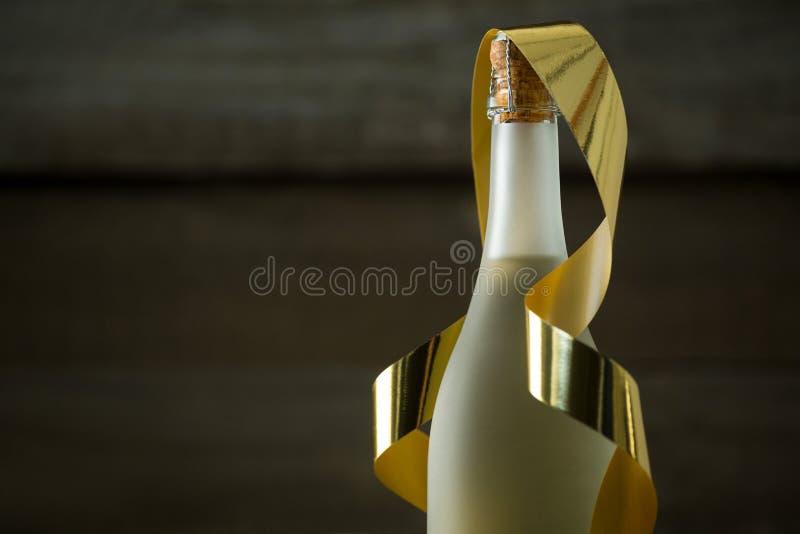 Champagne-fles met gouden lint tegen houten achtergrond stock fotografie
