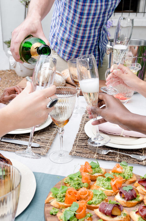 Champagne-fluiten en het roosteren onder vrienden stock fotografie