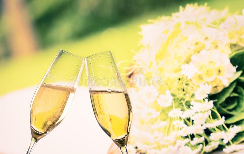 Champagne-fluiten met gouden bellen op de achtergrond van huwelijksbloemen stock afbeeldingen