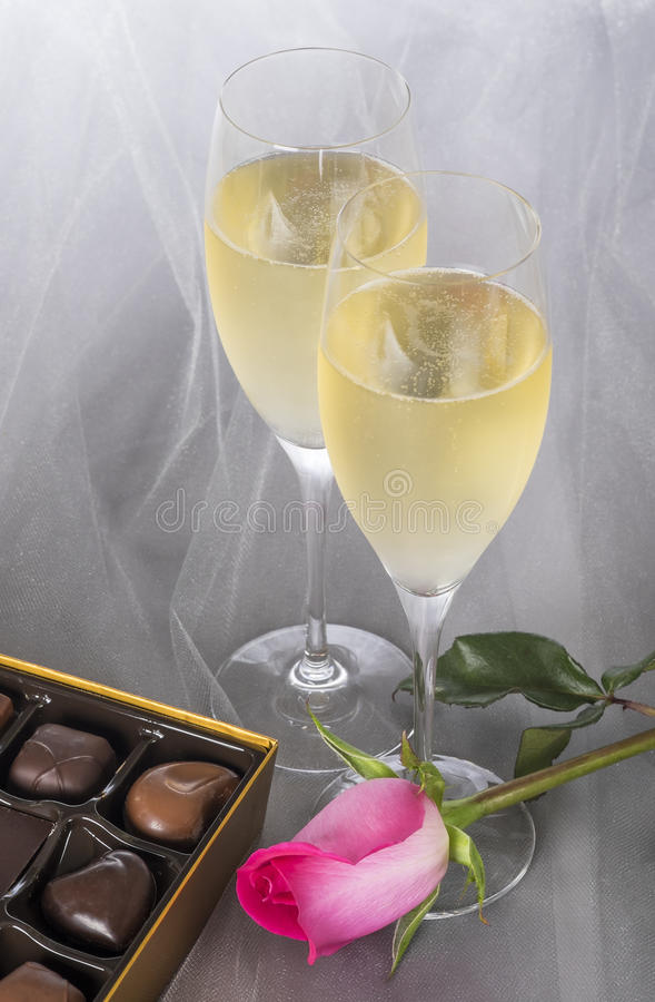 Champagne Flutes, chocolates gastrónomos, y una Rose rosada en Gray Tulle Background imagen de archivo