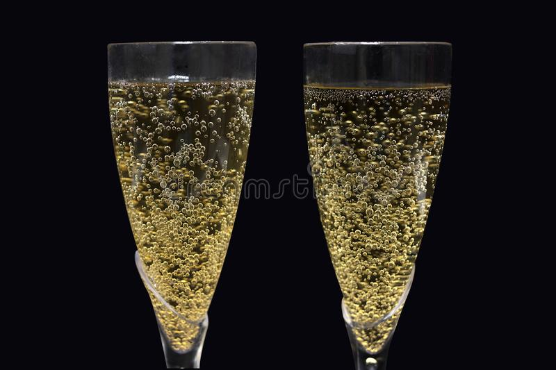Champagne In Flutes. Closeup of champagne in flutes, isolated on black stock photos
