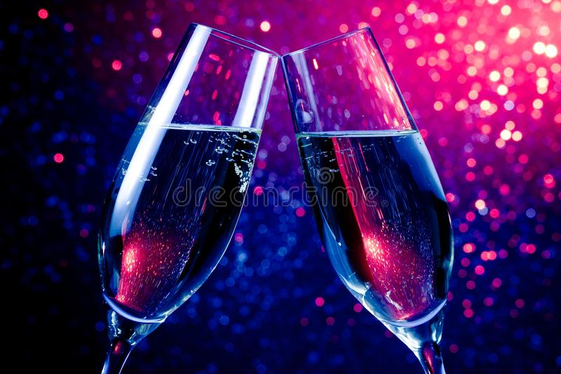 Champagne flutes with gold bubbles on blue tint light bokeh background. Pair of champagne flutes with gold bubbles make cheers on blue tint light bokeh royalty free stock images