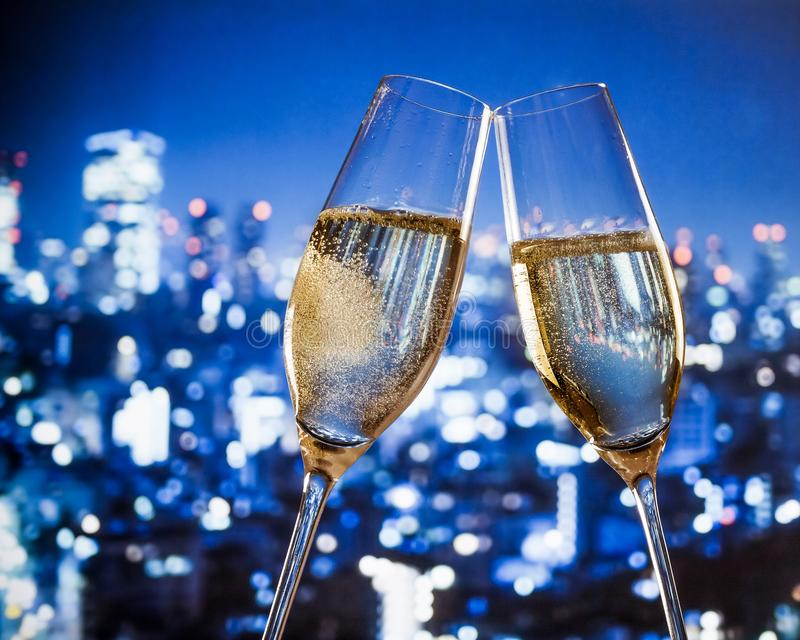 Champagne flutes with golden bubbles on blue city night lights background stock images