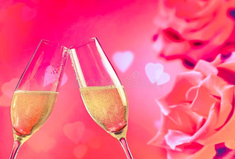 Champagne flutes with golden bubbles on roses flowers background royalty free stock photography