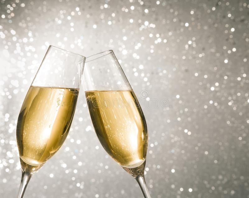 Champagne flutes with golden bubbles on silver light bokeh background. Champagne flutes with golden bubbles make cheers on silver light bokeh background with royalty free stock image