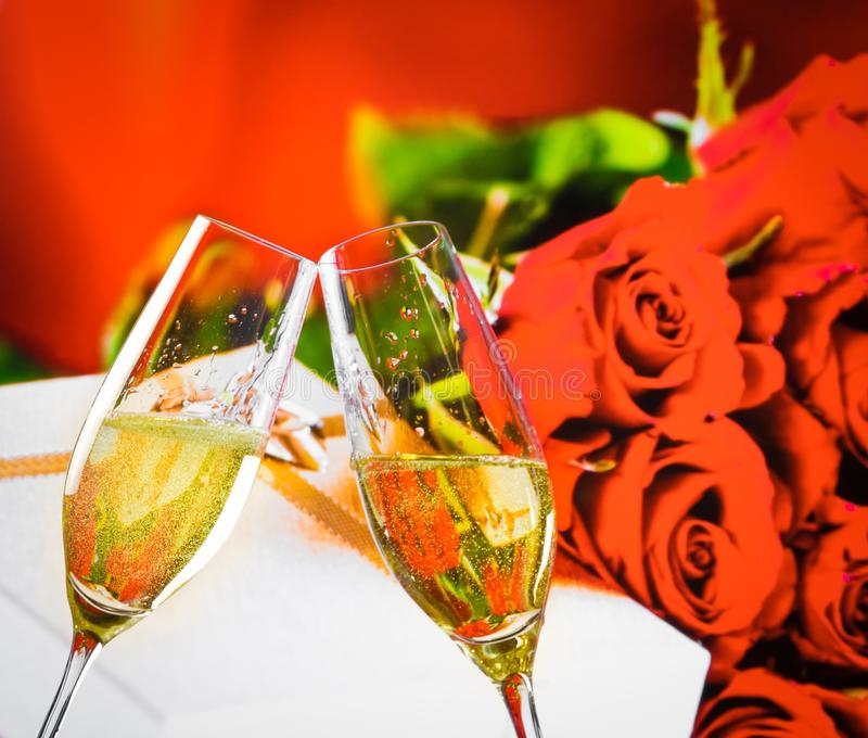 Champagne flutes with golden bubbles on wedding roses flowers background stock images