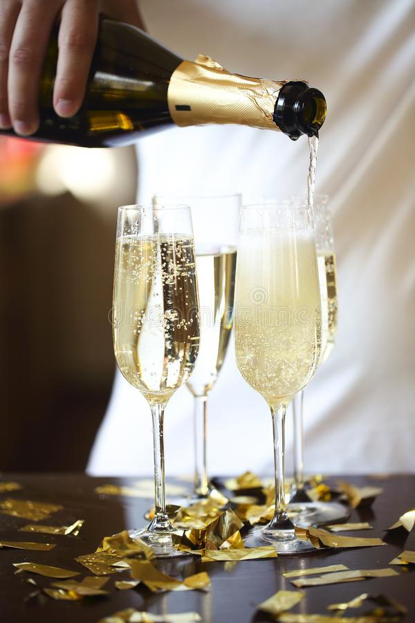 Champagne Flutes In Golden Sparkle Background with golden confetti. Man pouring sparkle wine stock images
