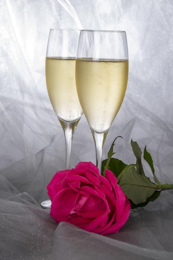 Champagne Flutes och en rosa färgros på Gray Tulle Background #2 arkivfoto