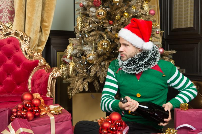 Champagne and the fun goes on. Man in santa hat hold new year presents. Merry Christmas and Happy New Year. Happy man stock photography