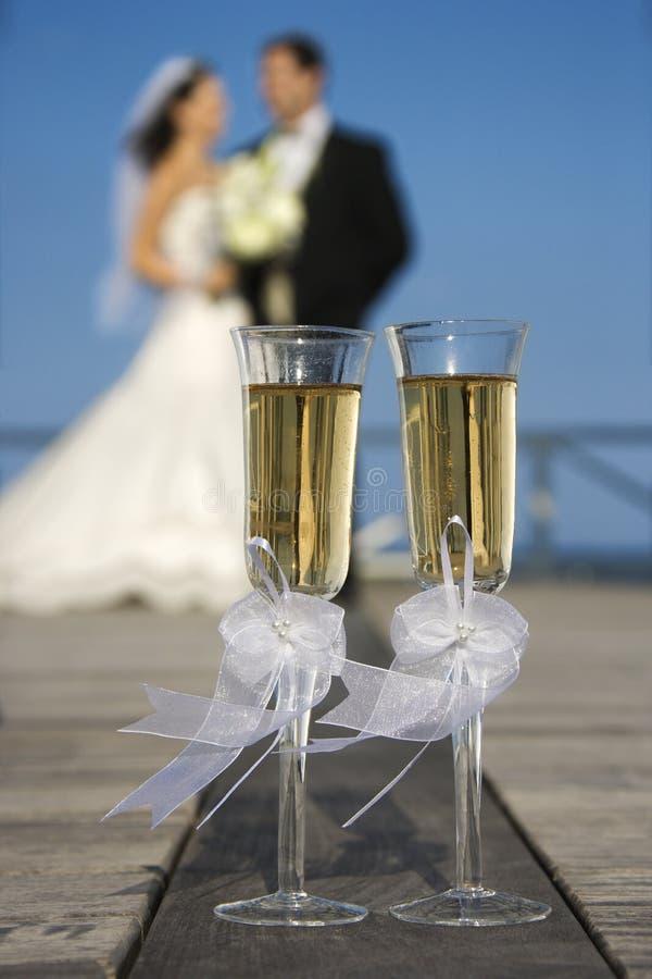 Champagne-Gläser mit Braut und Bräutigam im Hintergrund. stockfotografie