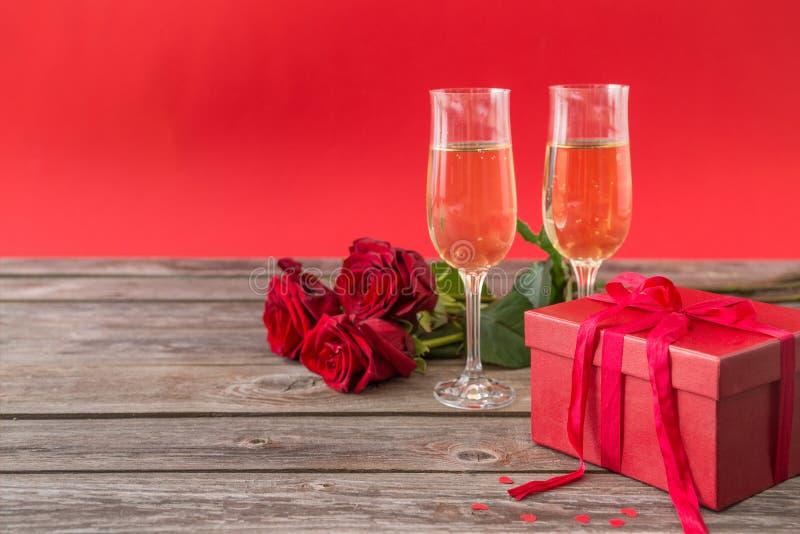 Champagne-Gläser, rote Geschenkbox und rote Rosen lizenzfreies stockbild