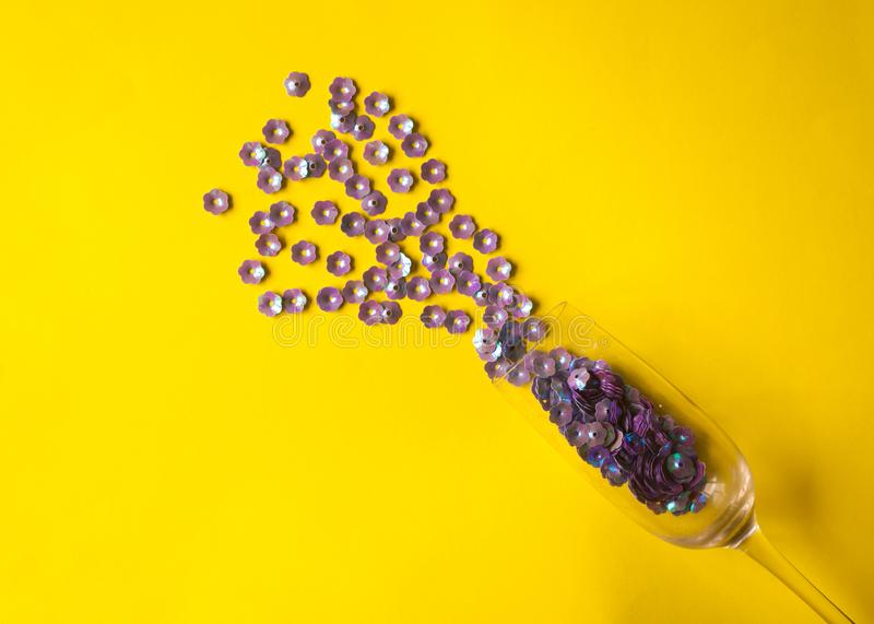 Champagne-glas met purpere bloemenconfettien op gele achtergrond royalty-vrije stock afbeelding