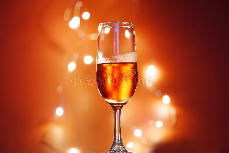 Champagne-glas op lijst tegen vage lichtenachtergrond - perspectief van glashelder wijnglas voor nachtpartij op royalty-vrije stock afbeeldingen