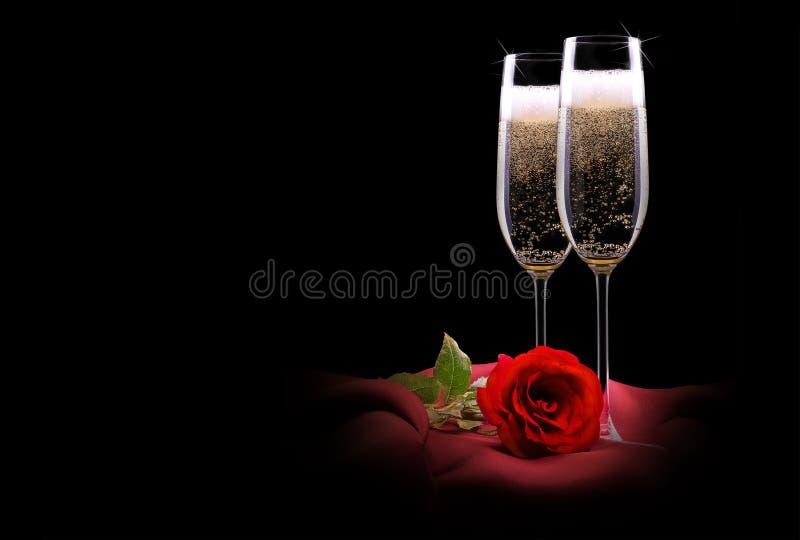 Champagne-glas op zwarte en rode zijde met bloem stock foto
