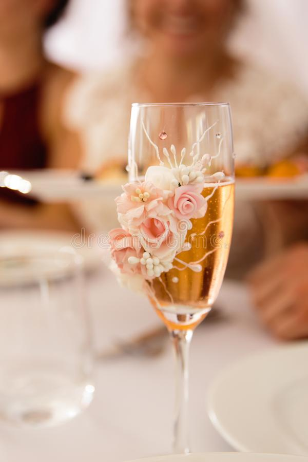 Champagne glass closeup with depth of field blur - Wedding Setup decoration during Reception - Tender pink and white royalty free stock photography