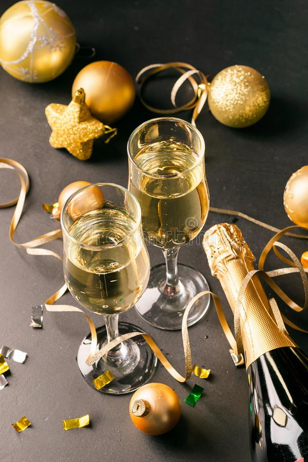 Champagne in glass goblets a bottle of New Year`s toys serpentine stars black background. New year christmas concept. stock images