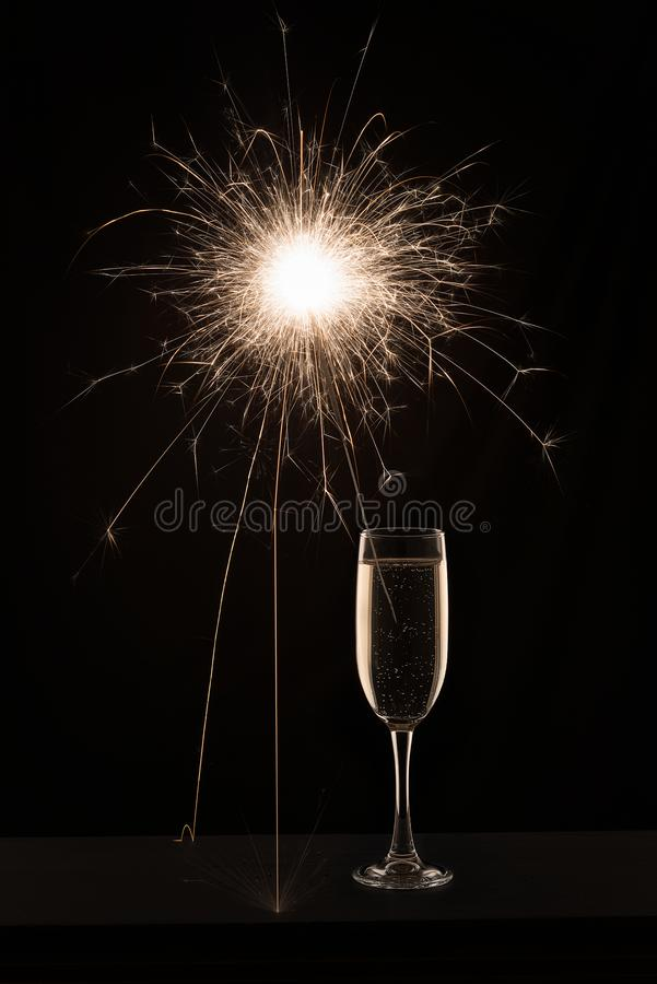 Champagne glass with lit sparkler against a dark background.  royalty free stock photography
