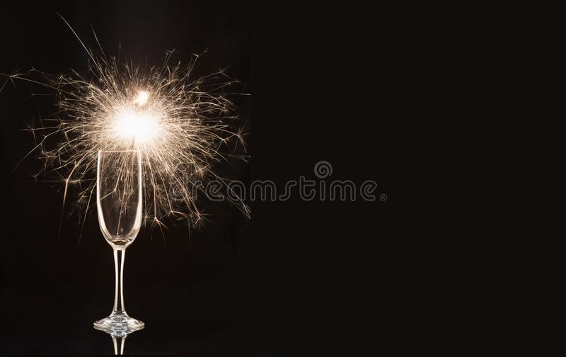 Champagne glass with lit sparkler against a dark background.  royalty free stock photos