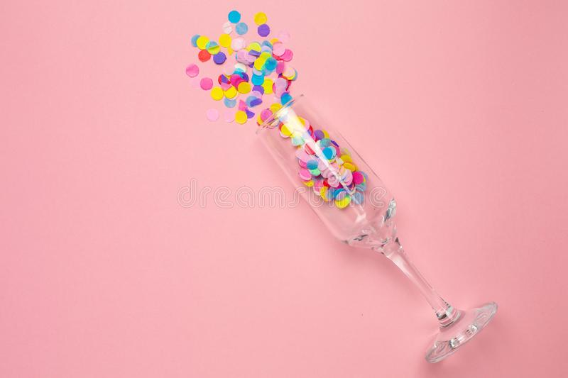 Champagne glass with multi-colored confetti on pink color paper background . Flat lay composition for birthday, mother day or. Champagne glass with multi-colored royalty free stock photography