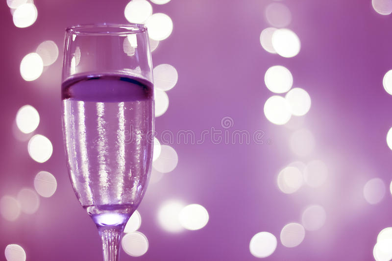 Champagne glass in party. Champagne sparkling wine glass in disco party at night with defocused festive Christmas and New Year lights in nightclub stock photos