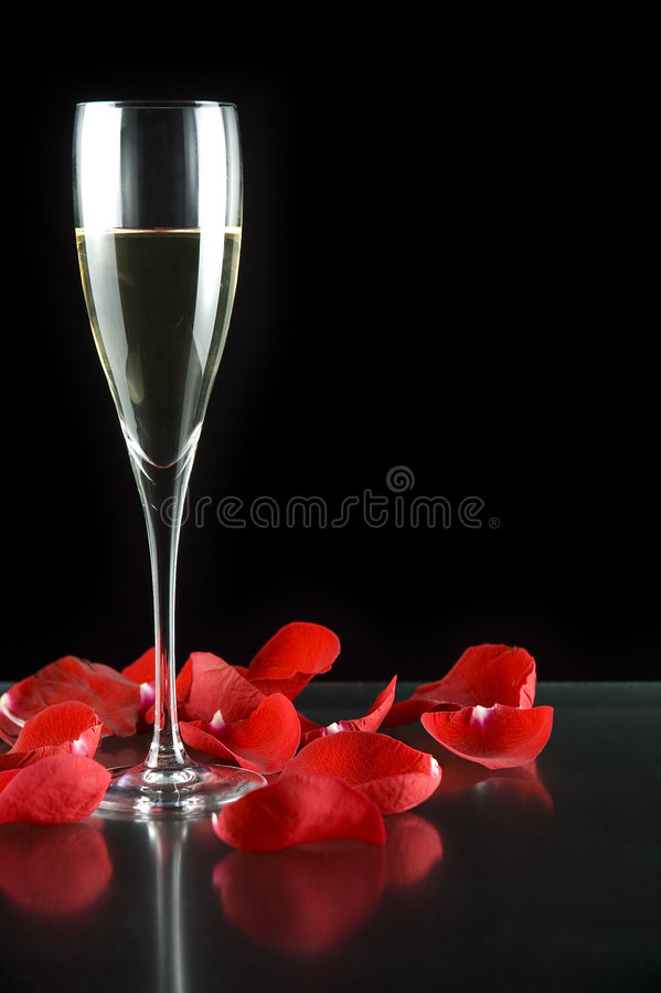 Champagne glass and petals stock photos