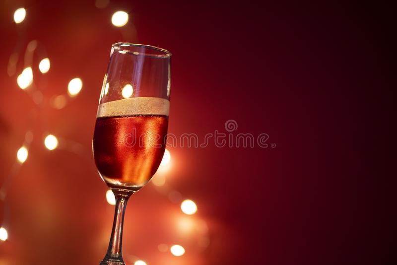 Champagne glass on table against blurred lights background - perspective of crystal clear wine glass for night party on the stock photo