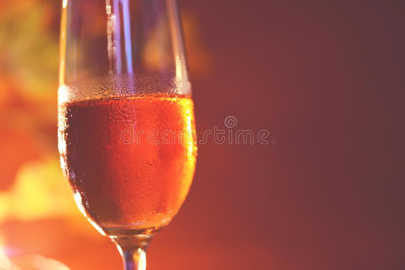 Champagne glass on table against blurred lights background - perspective of crystal clear wine glass for night party on the royalty free stock photo