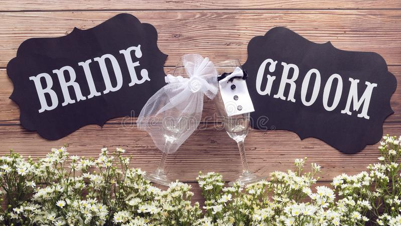 Champagne glass in wedding dress with Bride and Groom text sign on wooden background decorated with tiny white flower, vintage stock photography