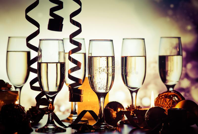 champagne glasses against holiday lights ready for New Year& x27;s eve party royalty free stock images