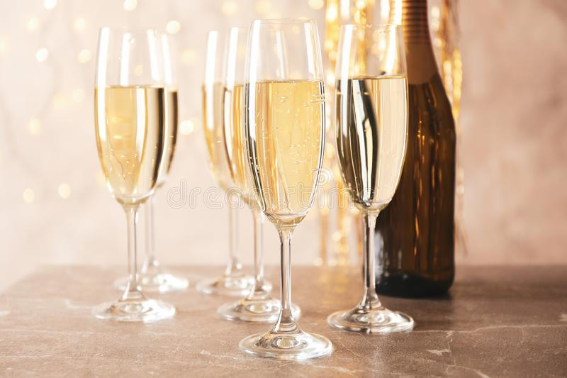Champagne glasses and bottle against blurred lights background royalty free stock photography