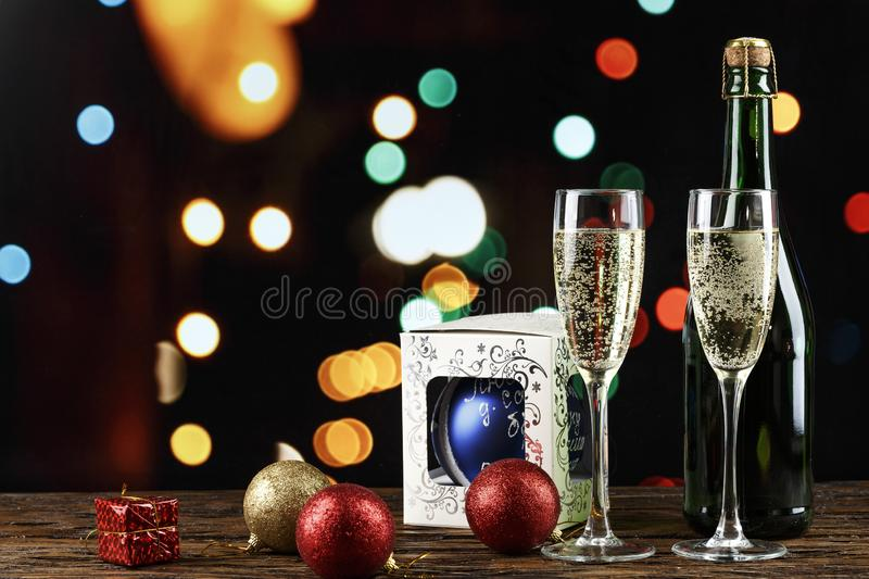 Champagne in glasses and in a bottle and toys on the Christmas tree on the background of bokeh. Christmas background. space for text stock photography