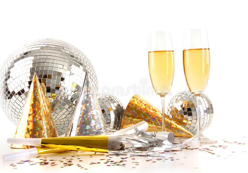 Champagne glasses and disco ball. Champagne glasses with gold party hats and big disco ball royalty free stock image