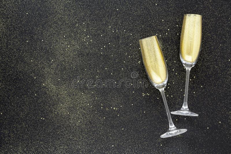 Champagne glasses filled with glitter on a black background. New Year Christmas eve celebration background. Christmas card. royalty free stock photos