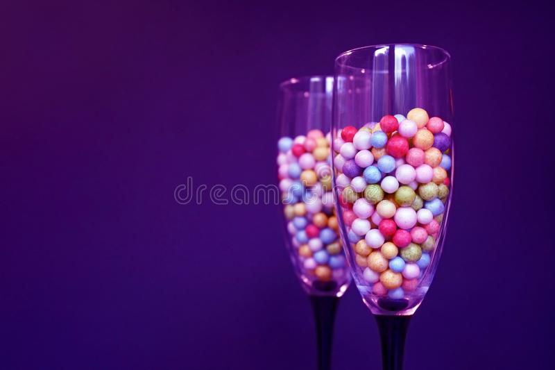 Champagne glasses filled with small colorfull foam balls on dark purple background stock photos