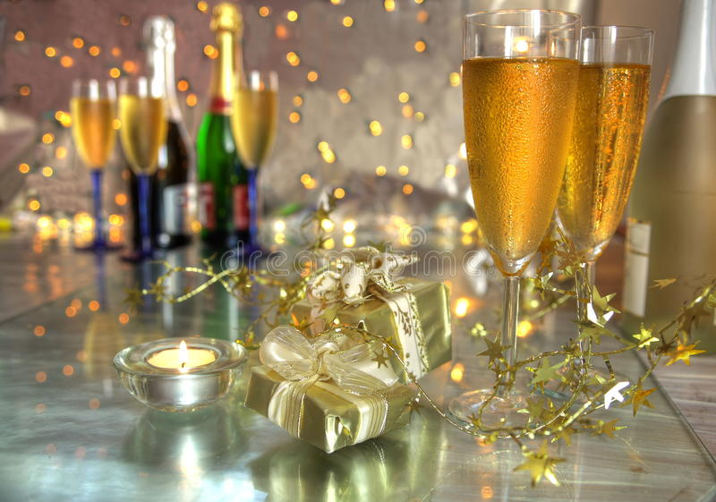 Champagne in glasses, gift boxes and lights royalty free stock photography