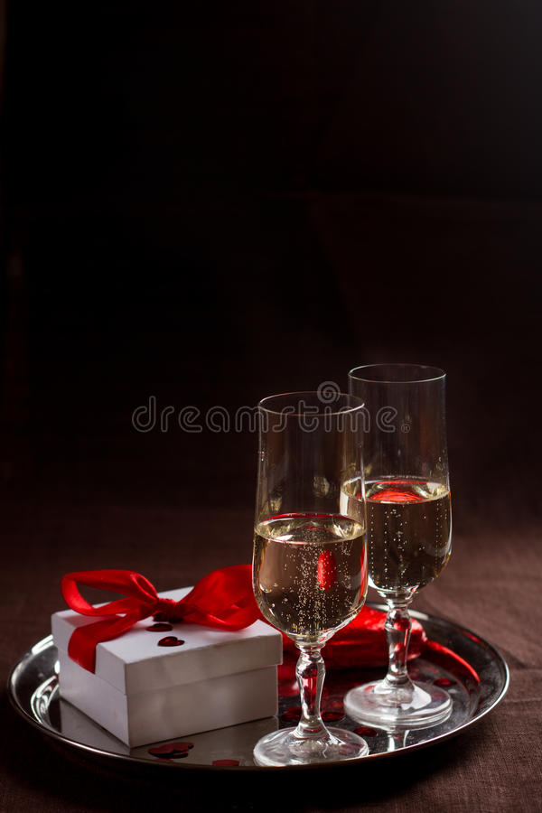 Champagne glasses, gift and hearts. For celebrating Valentines Day or wedding, selective focus royalty free stock photography