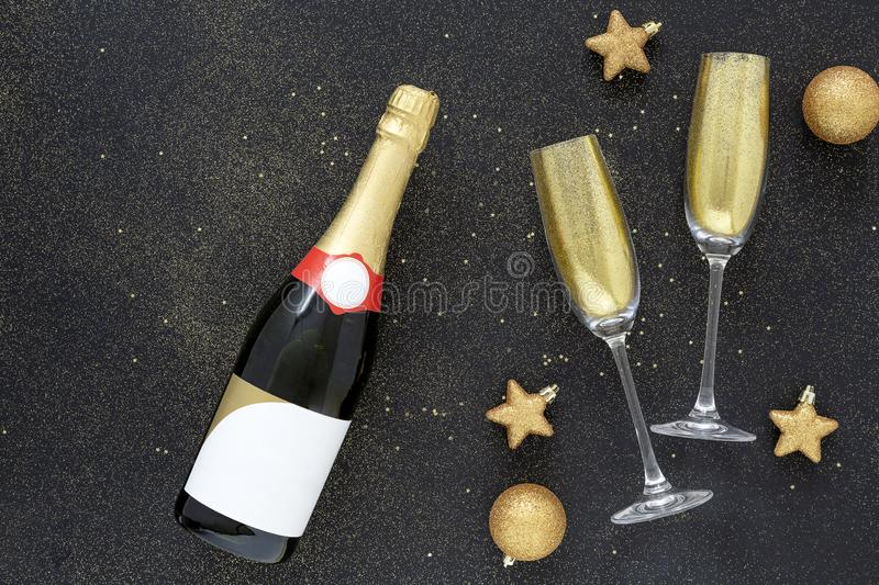 Champagne glasses with golden confetti and a bottle of champagne on black background. Christmas card. Celebrate party concept. stock image