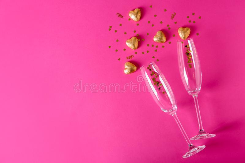 Champagne glasses and heart shaped candies in golden foil on color background stock photo