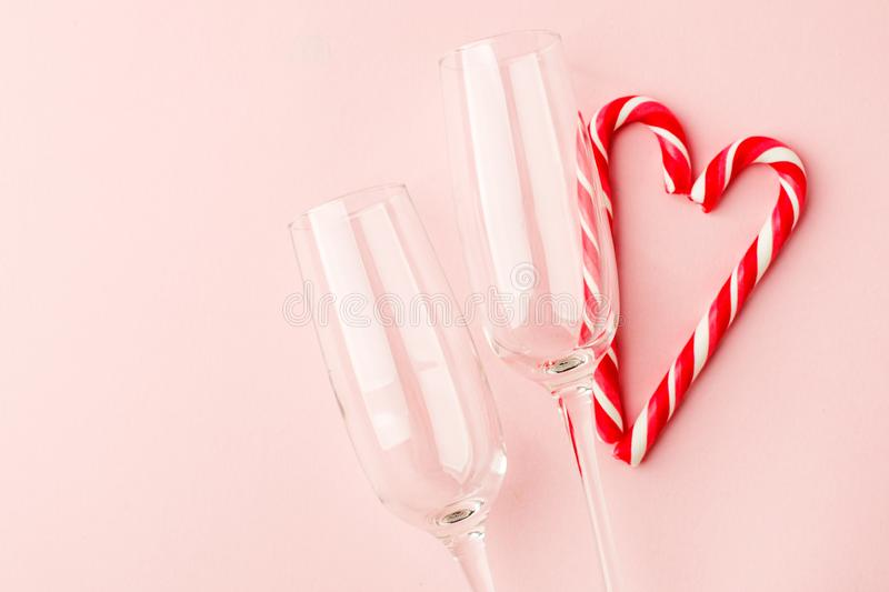 Champagne glasses and heart shaped sweets holiday template. Christmas, Birthday or Valentines`day over pink background. Top view stock image