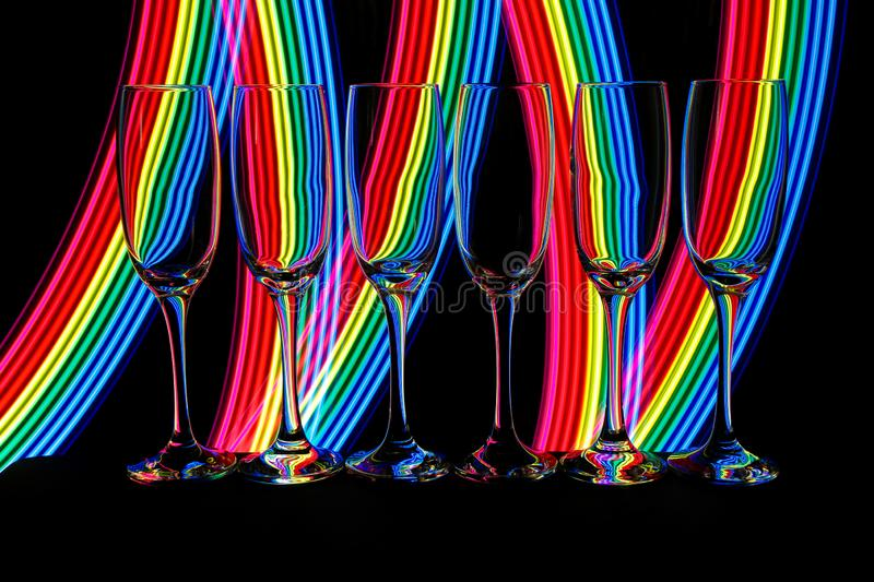 Champagne glasses with neon light behind royalty free stock image