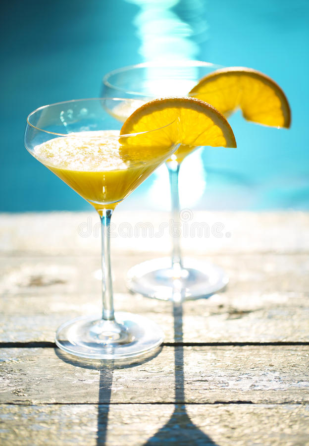 Champagne glasses with orange slice Mimosa cocktail. Champagne glasses with orange slice. Mimosa cocktail. Summer pool party stock images
