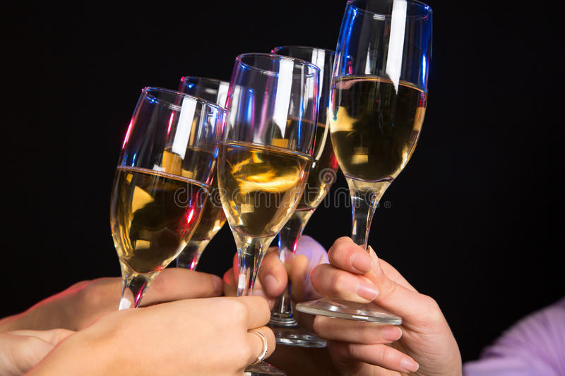 Champagne glasses during toast. Photo of champagne glasses during toast at party royalty free stock image